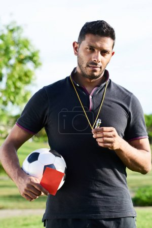 Handsome mixed race soccer referee holding football and whistle