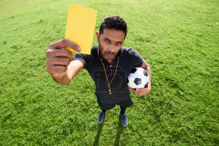 High angle view of mixed race soccer referee showing yellow card to camera