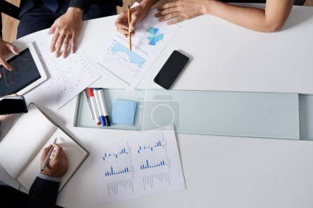 Business team analyzing charts and graphs during the meeting, view from above