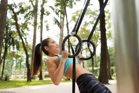 Vietnamese Yong woman performing exercise with gymnastic rings