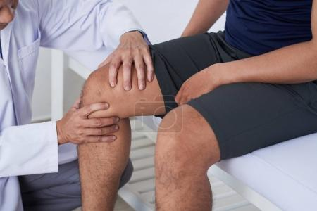Photo for Close-up image of doctor cheeking knee of male patient - Royalty Free Image
