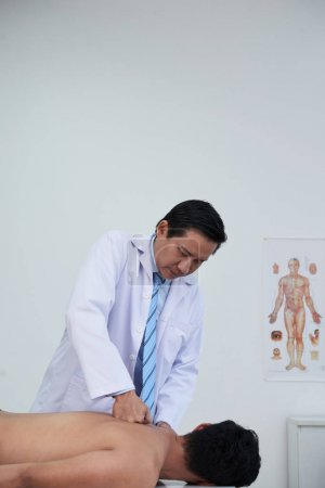 Therapist giving back massage to patient in clinic