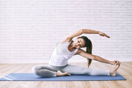 Photo for Young Asian woman exercising on the floor in yoga studio - Royalty Free Image