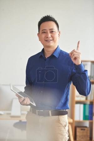 Portrait of smiling Asian businessman rising finger up