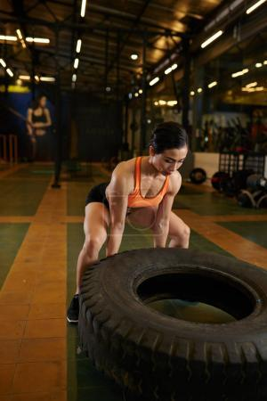 Strong Vietnamese woman turning huge tyre during cross fit training