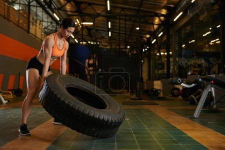 Strong young woman exercising with big heavy tyre