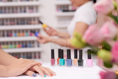 Photo for Hands of female client with colorful nails in manicure salon - Royalty Free Image