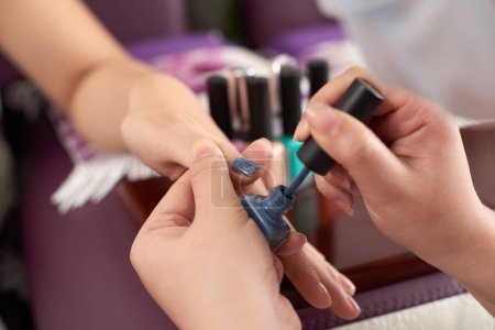 Photo for Close-up image of manicurist applying dark grey nail polish - Royalty Free Image