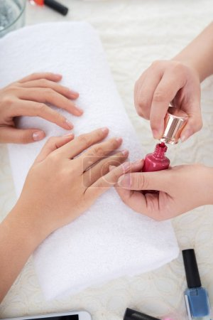 Photo for Hands of manicurist applying red nail polish to the nails of client - Royalty Free Image