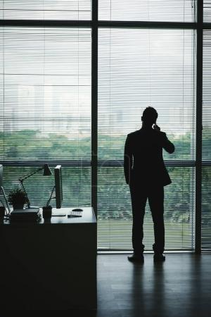 Businessman looking through the office window when talking on the phone