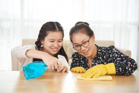 Teenage Asian girl and her grandmother trying to get rid of the spot on table surface