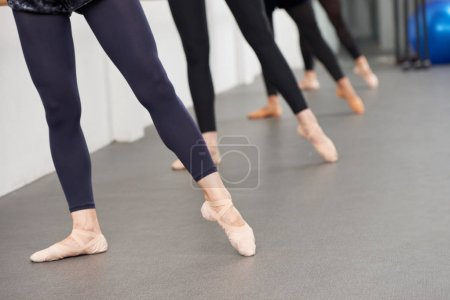 Photo for Ballerinas pointing toes when performing exercise at handrail - Royalty Free Image