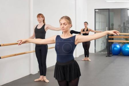 Pretty ballet instructor showing exercise to women