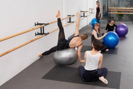 Female instructor showing exercise on fit ball to young women