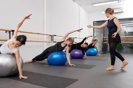 Instructor looking how women performing exercise on fit balls