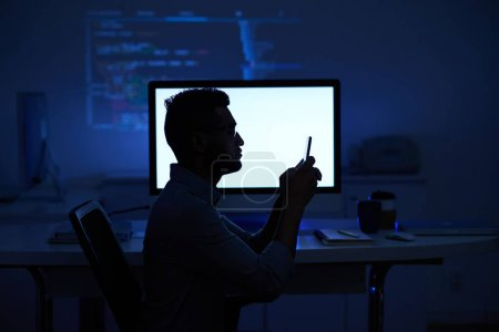 Silhouette of software developer reading text message at glowing computer screen