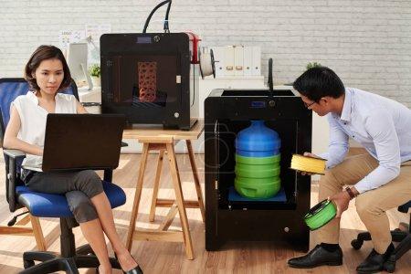 Designer looking how 3D printer making big plastic bottle