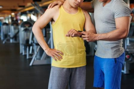 Fitness trainer explaining client how tracker works