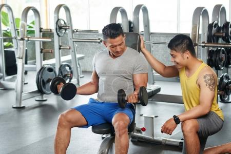 Fitness instructor controlling how bodybuilder working out with weights