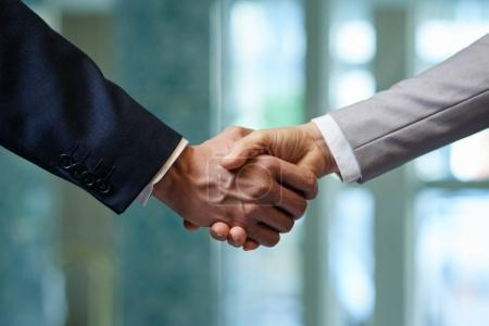 Close-up shot of firm handshake as sign of trusted partnership, blurred background