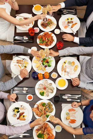 Photo for Group of people clinking glasses at dinner table with seafood, view from above - Royalty Free Image