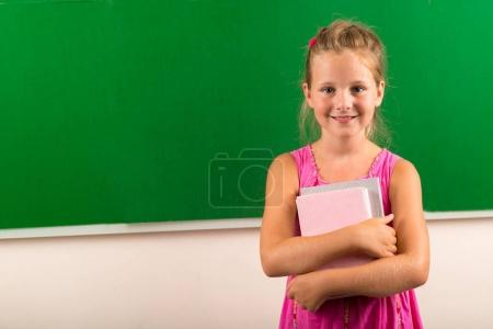 Portrait of happy schoolgirl with textbooks standing at chalkboard in class