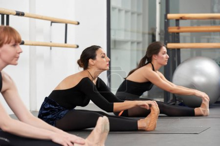 Young women in ballet school stretching