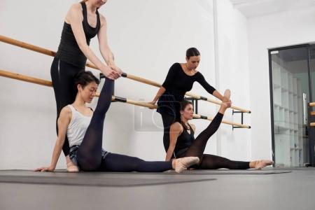 Young women in ballet school with instructor, stretching exercise