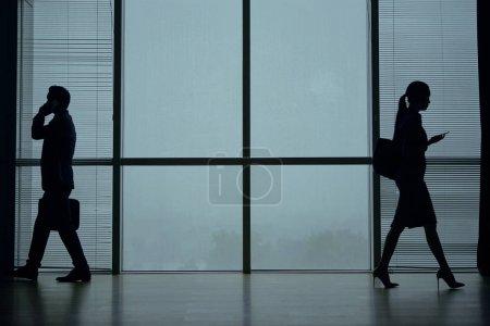 Photo pour Silhouettes de gens d'affaires parlant au téléphone et à la poste lorsqu'ils marchent dans un bureau moderne avec de grandes fenêtres panoramiques - image libre de droit