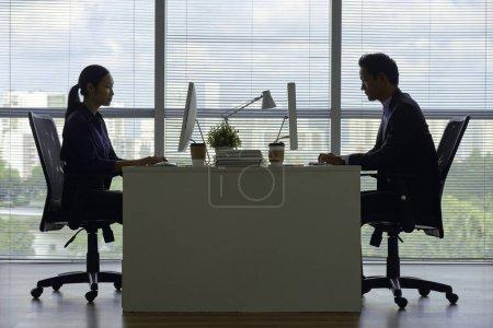 Photo pour Vue latérale d'une équipe de gens d'affaires vietnamiens sérieux qui travaillent sur des ordinateurs à une table de bureau - image libre de droit