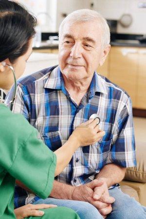 Lächelnder älterer Mann schaut Krankenhausangestellte in grünem Gestrüpp an und hört seinem Herzschlag zu, wenn er ihn zu Hause besucht