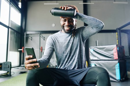 Photo for Exhausted but happy fit man following guide in fitness application when working out in gym - Royalty Free Image
