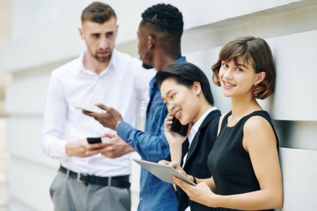 Photo for Pretty young smiling businesswoman standing outdoors with coworkers, holding tablet computer, leaning on wall and looking at camera - Royalty Free Image