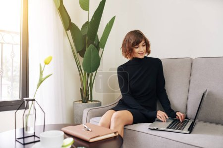 Photo for Pretty smiling young woman in black dress sitting on sofa and answering e-mails on her laptop - Royalty Free Image
