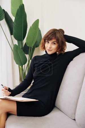 Photo for Portrait of young beautiful woman in short black dress sitting on comfy sofa at home and taking notes in planner - Royalty Free Image