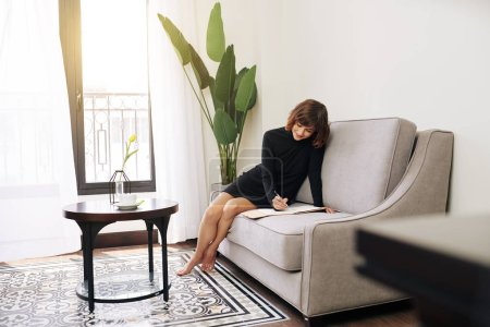 Photo for Lovely smiling barefoot woman sitting on sofa and writing in planner her creative business ideas - Royalty Free Image