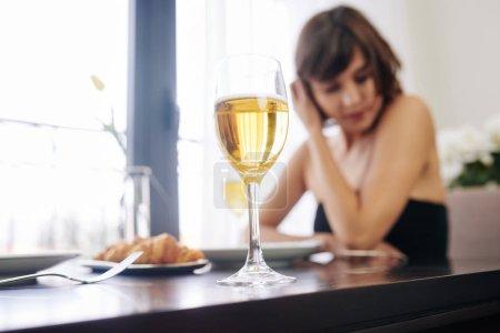 Photo pour Verre de vin blanc de jeune femme assise à la table du restaurant seule et attendant sa date - image libre de droit