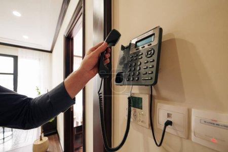 Photo pour Image recadrée de l'homme utilisant le téléphone dans la chambre d'hôtel pour commander de la nourriture et des boissons ou un service de nettoyage - image libre de droit