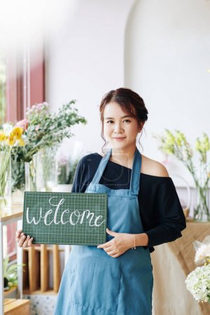 Photo for Portrait of young Asian woman in apron holding welcome signboard and inviting customer to her flower shop - Royalty Free Image