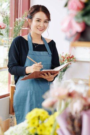 Photo pour Portrait de jeune propriétaire confiant fleuriste planification des développements de sa petite entreprise - image libre de droit