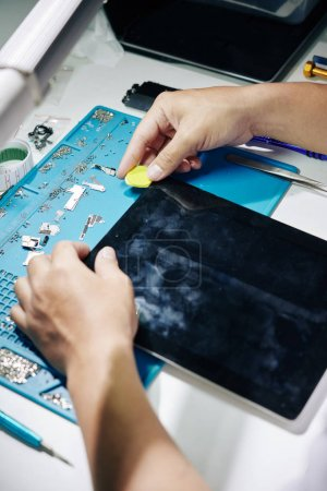 Photo for Process of repairman removing screen of tablet computer that does not work - Royalty Free Image