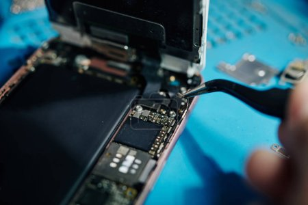 Photo for Close-up image of smartphone repairman using tweezers to remove antenna cable when trying to get access to the speaker - Royalty Free Image