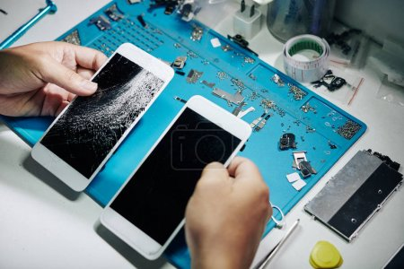 Photo for Repairman comparing new and cracked smartphone screens - Royalty Free Image