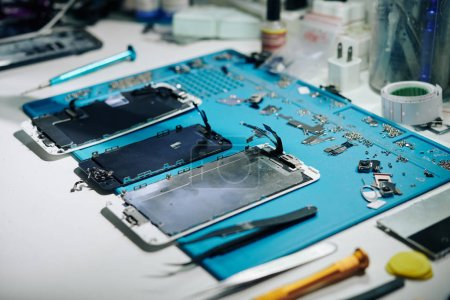 Photo for Parts and details of disassembled smartphone on desk of repairman - Royalty Free Image