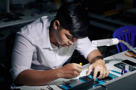 Photo for Concentrated young Vietnamese repairman using screwdriver to assemble smartphone after fixing it - Royalty Free Image