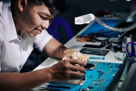 Photo for Smiling Asian man repairing smartphone under light of led lamp at his desk - Royalty Free Image
