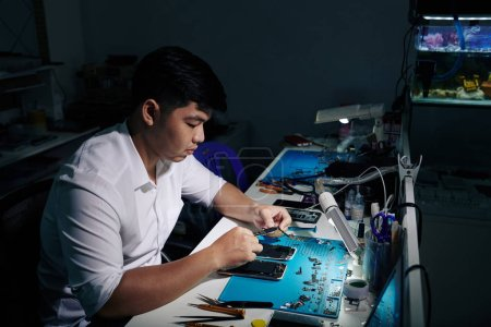 Photo for Serious repairman trying to figure out how to assemble broken smartphone - Royalty Free Image