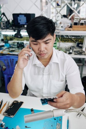 Photo for Confused repairman calling coworker when having some problems with fixing smartphone for customer - Royalty Free Image