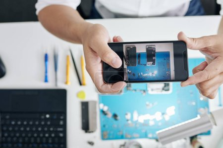 Photo for Photo of disassembled smartphone on screen of phone in hands of repairman - Royalty Free Image