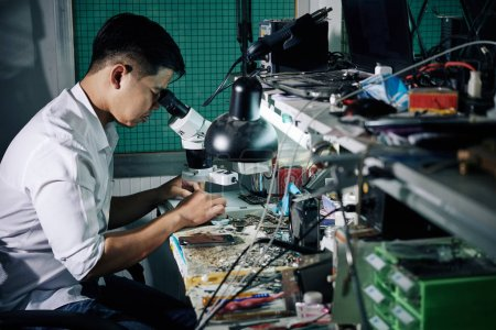 Photo for Repairman using microscope when fixing small details in smartphone - Royalty Free Image